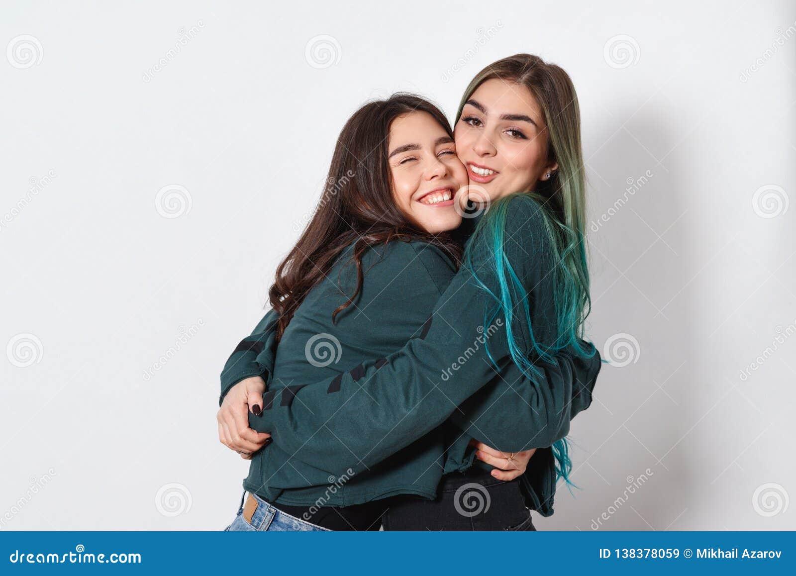Dwa kobiety dziewczyny przyjaciół śmieszny szczęśliwy uścisk na białym tle kobiety przyjaźń, siostry, młodość