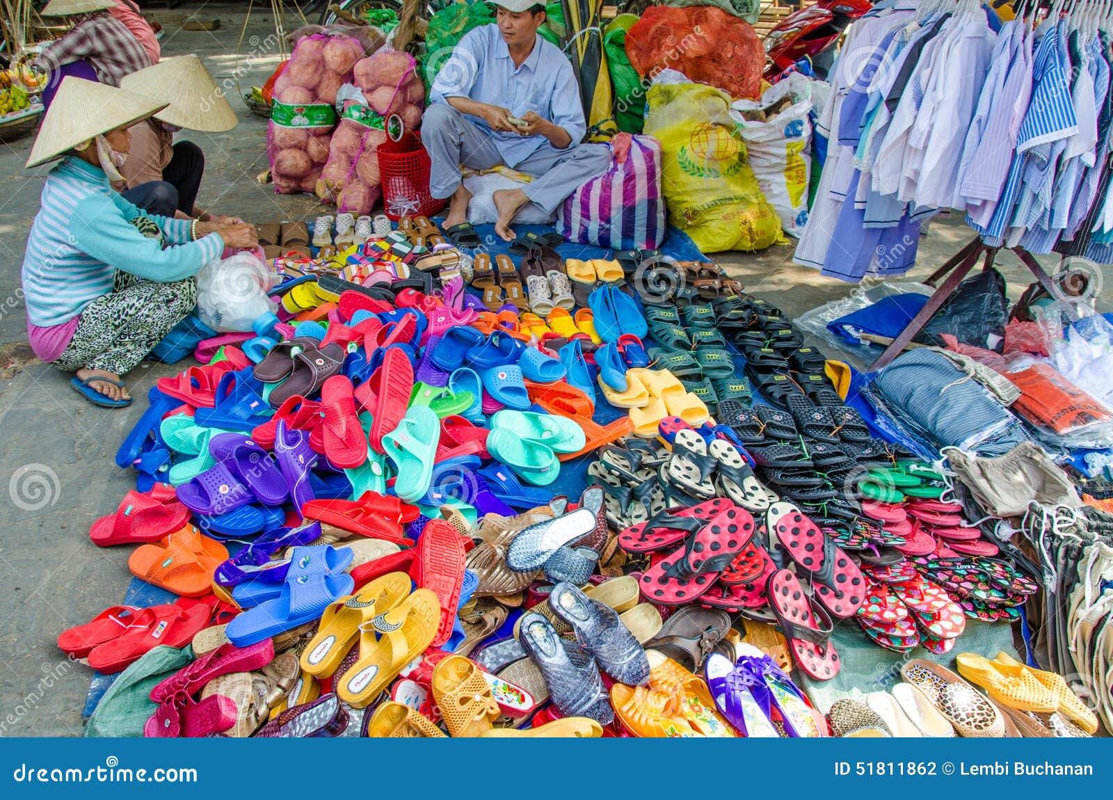 Dwa kobiety egzamininują kolorowych buty dla sprzedaży i sandały przy plenerowym rynkiem w Chan Maj, Wietnam