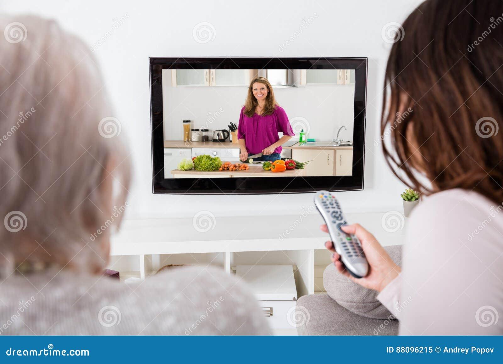 Dwa kobiety Ogląda Kulinarnego przedstawienie Na telewizi