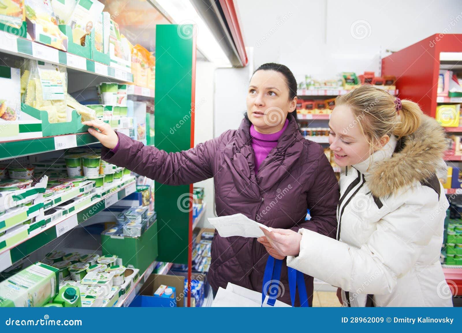 Dwa kobiety przy supermarketa nabiału zakupy