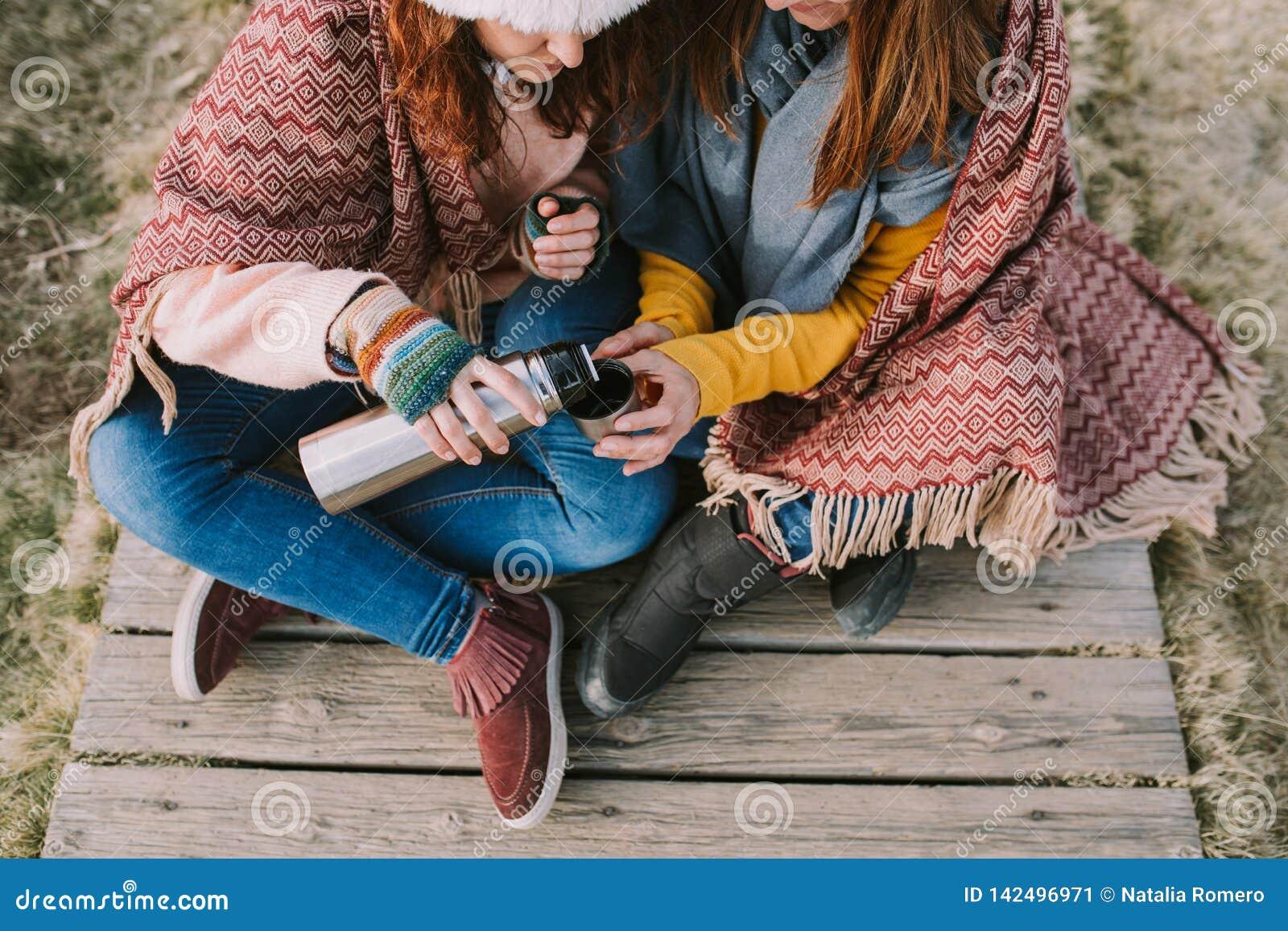 Dwa kobiety siedzi w łąkowej części filiżanka rosół