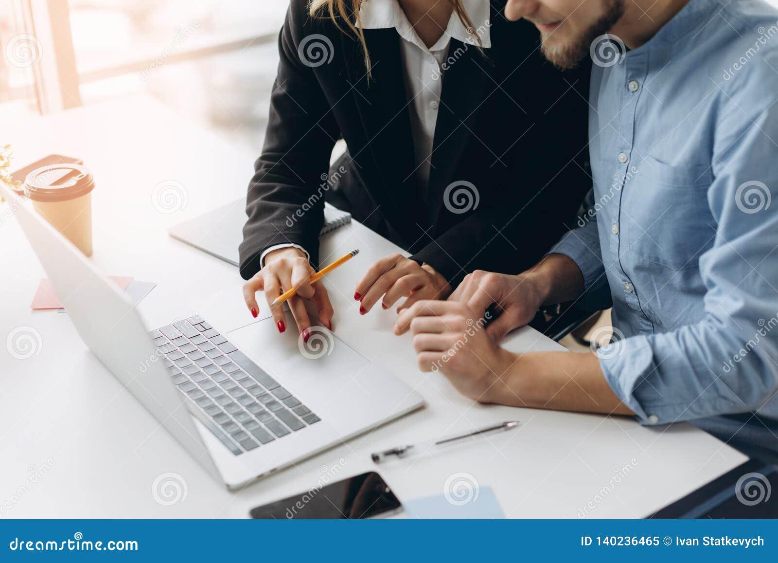 Dwa ludzie biznesu pracuje na laptopie z biznesowym dokumentem, wykresu diagramem i kalkulatorem na biuro stole,