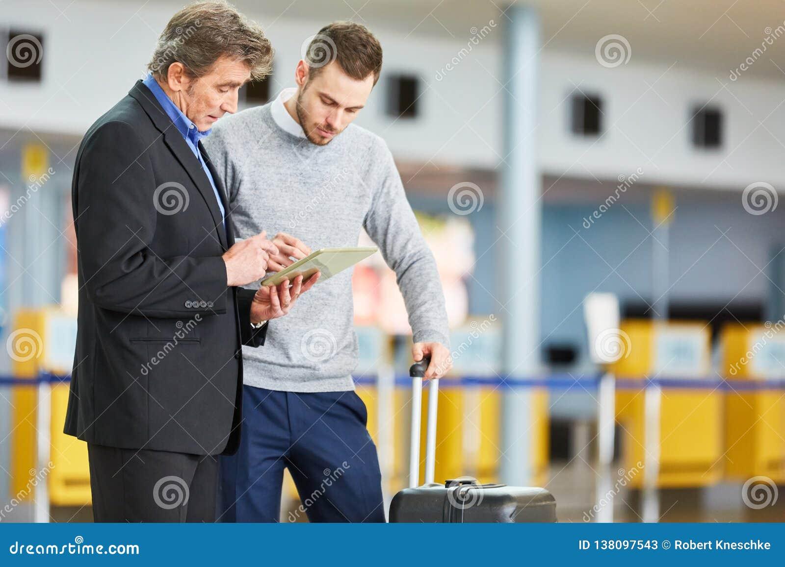 Dwa ludzie biznesu z pastylką w lotniskowy śmiertelnie