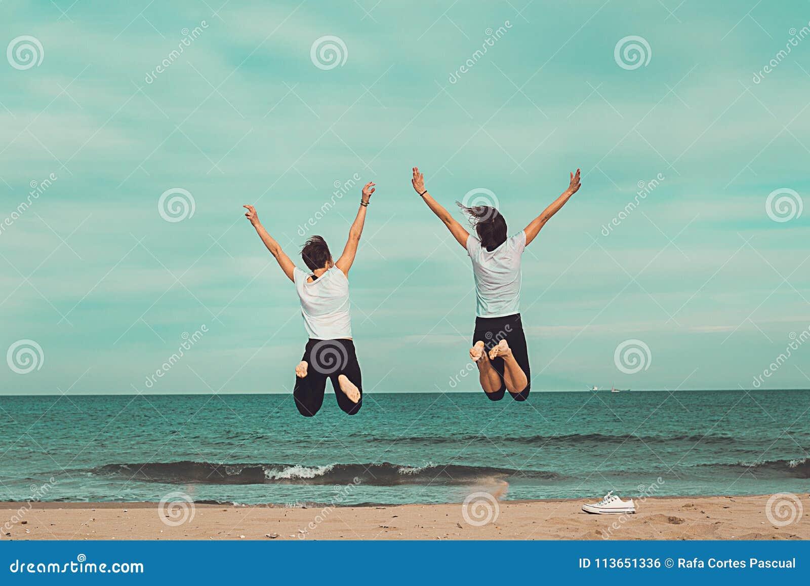 Dwa ludzie skacze morzem Pojęcie zabawa na plaży