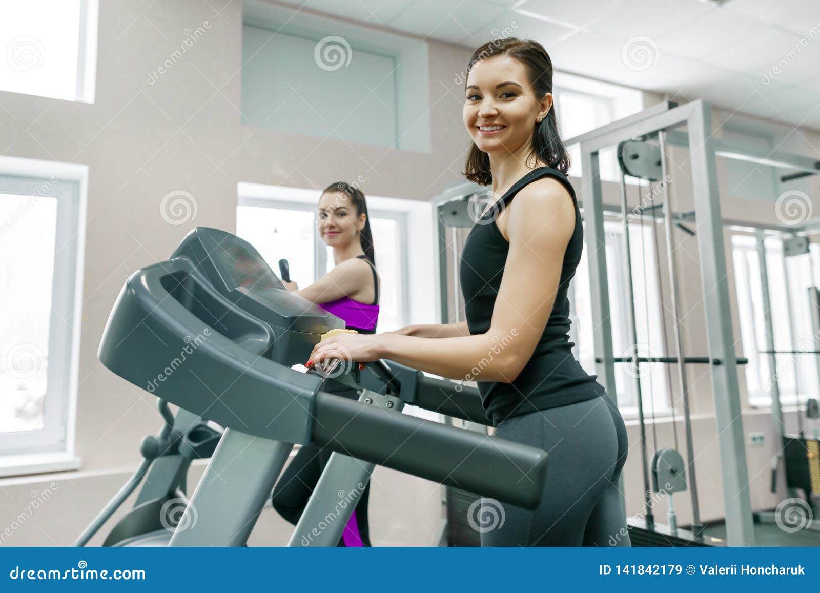 Dwa młodej sprawności fizycznej zdrowej kobiety na karuzeli w sporta nowożytnym gym Sprawność fizyczna, sport, szkolenie, ludzie