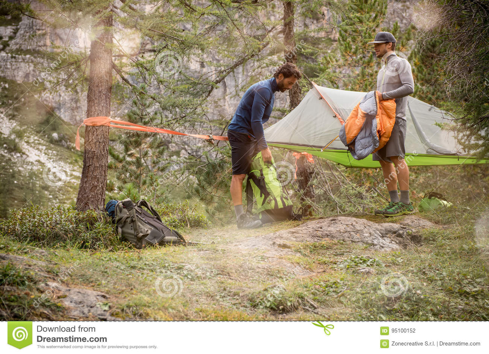 Dwa mężczyzna przygotowywa wiszących namiotowych campingowych pobliskich lasowych drewna Grupa przyjaciele zaludnia lato przygody