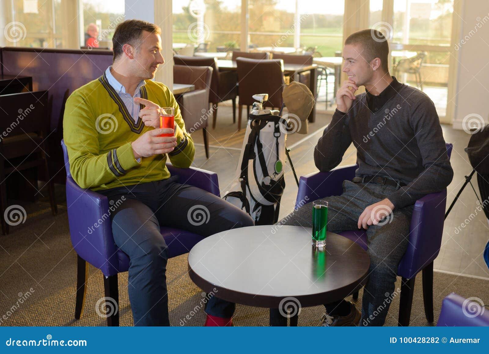 Dwa mężczyzna siedzącego w prętowym mieć napój