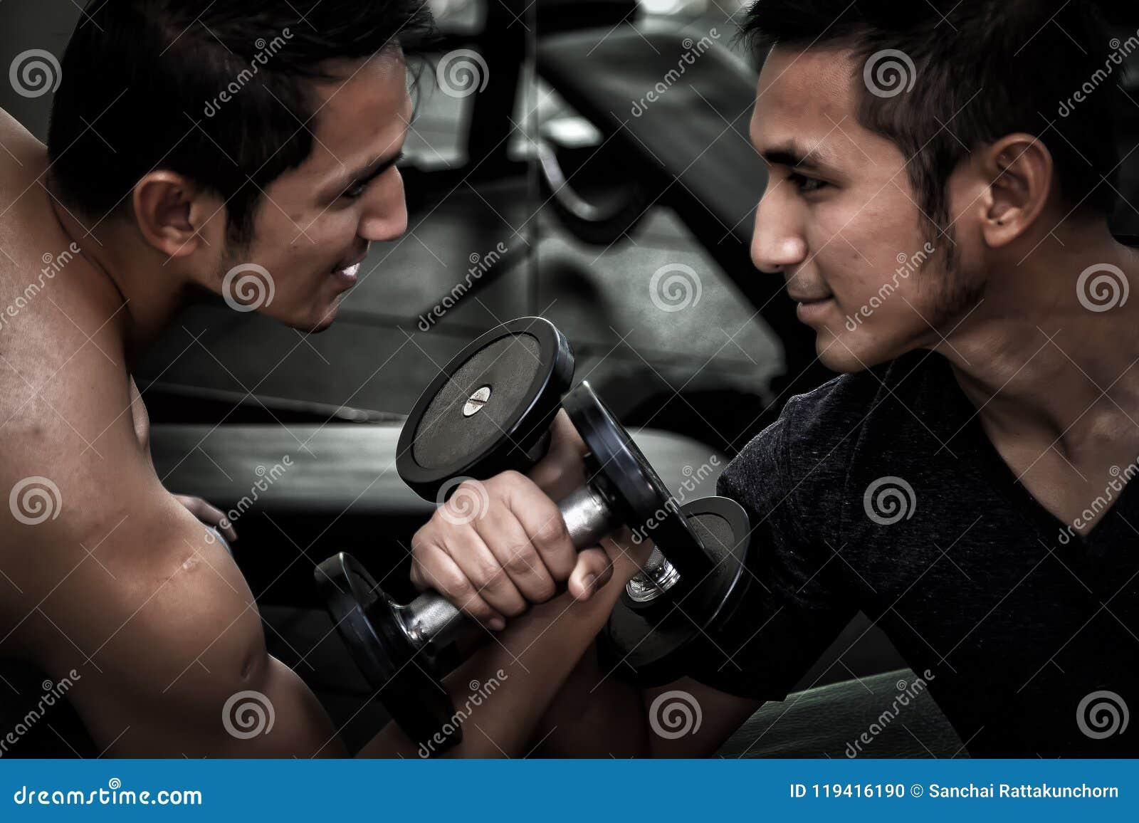 Dwa mężczyzna use dumbbell ćwiczenia Azjatycki udźwig mocuje się c
