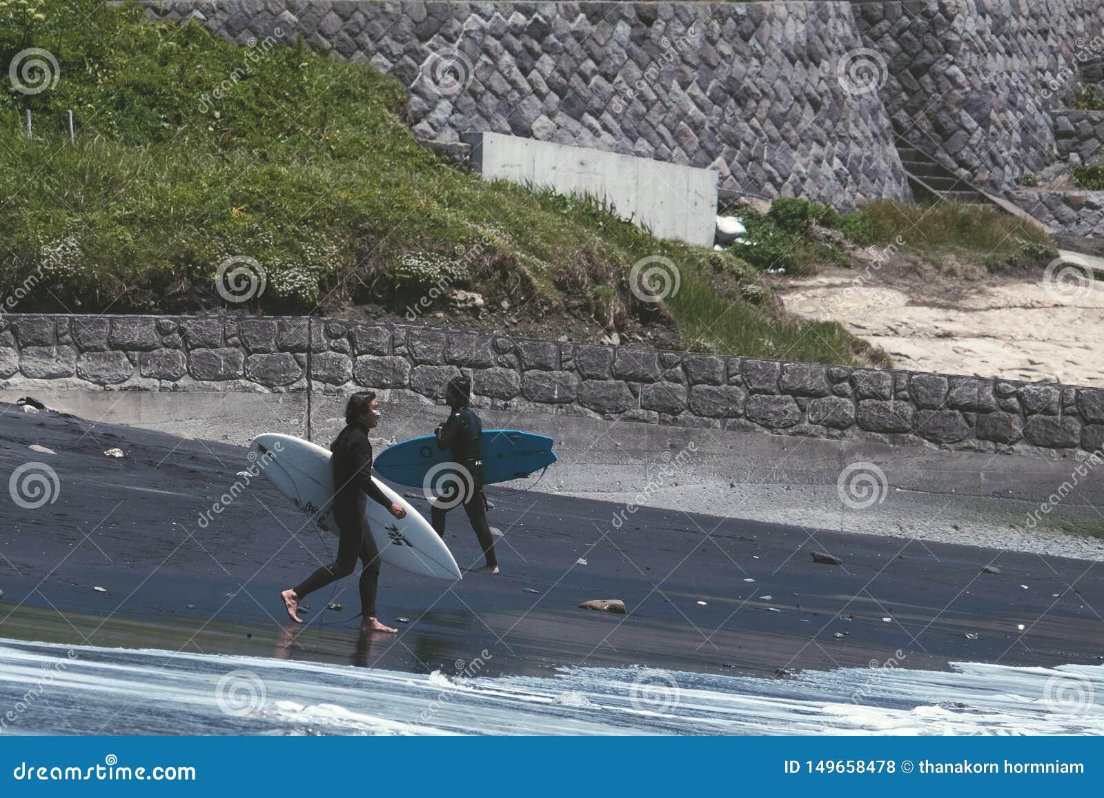 Dwa mężczyzny chodzi na czarnej plaży surfować