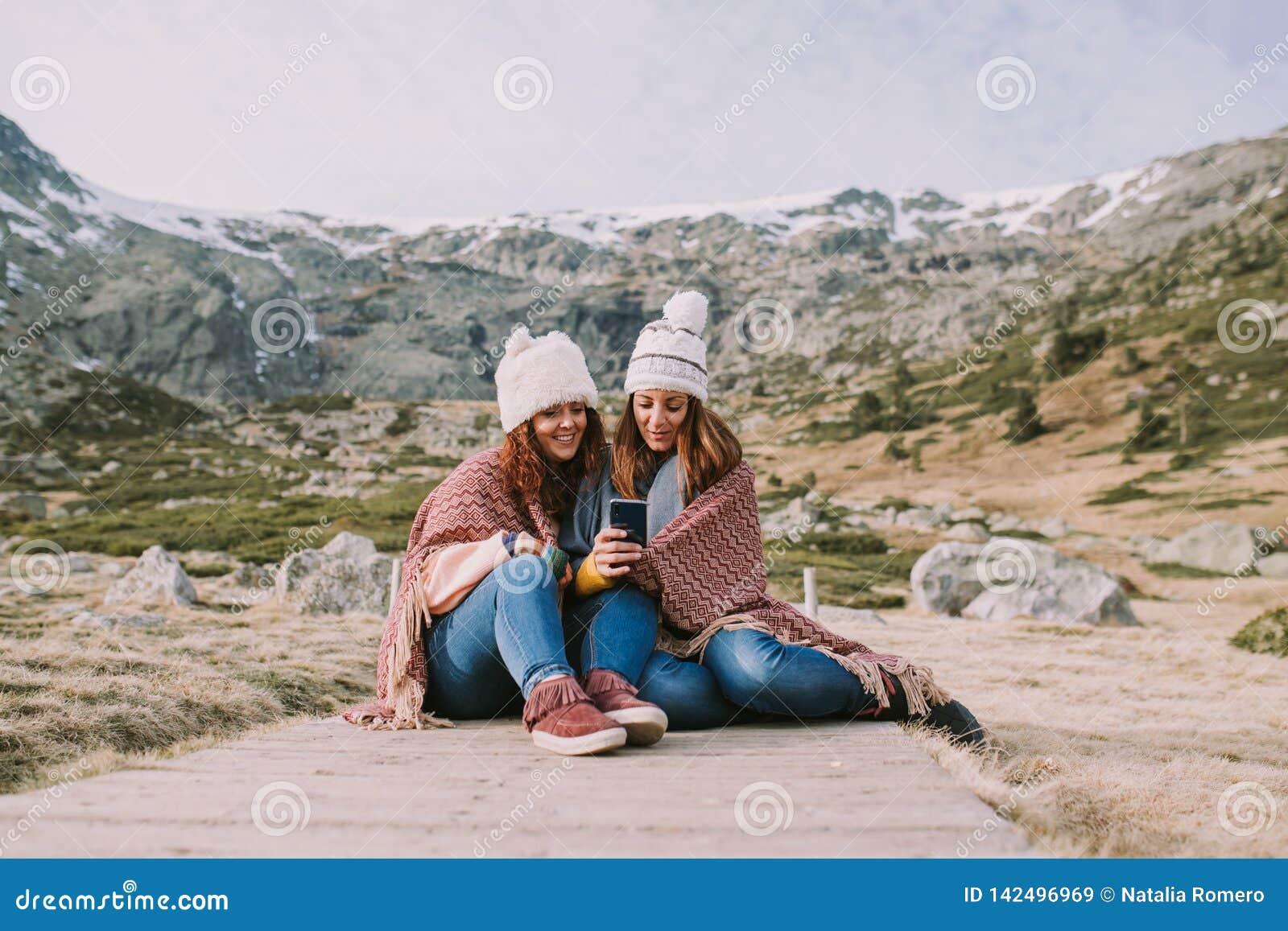 Dwa młoda dziewczyna przyjaciela siedzi w łąkowym spojrzeniu przy coś na telefonie