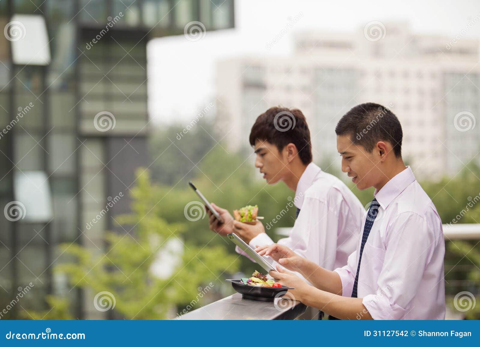 Dwa młodego biznesmena pracuje outdoors i je nad przerwa na lunch