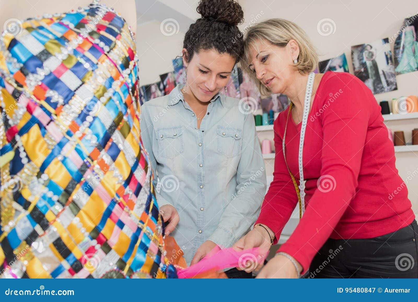 Dwa młodego pięknego żeńskiego krawczyny pracuje w krawczyny robią zakupy