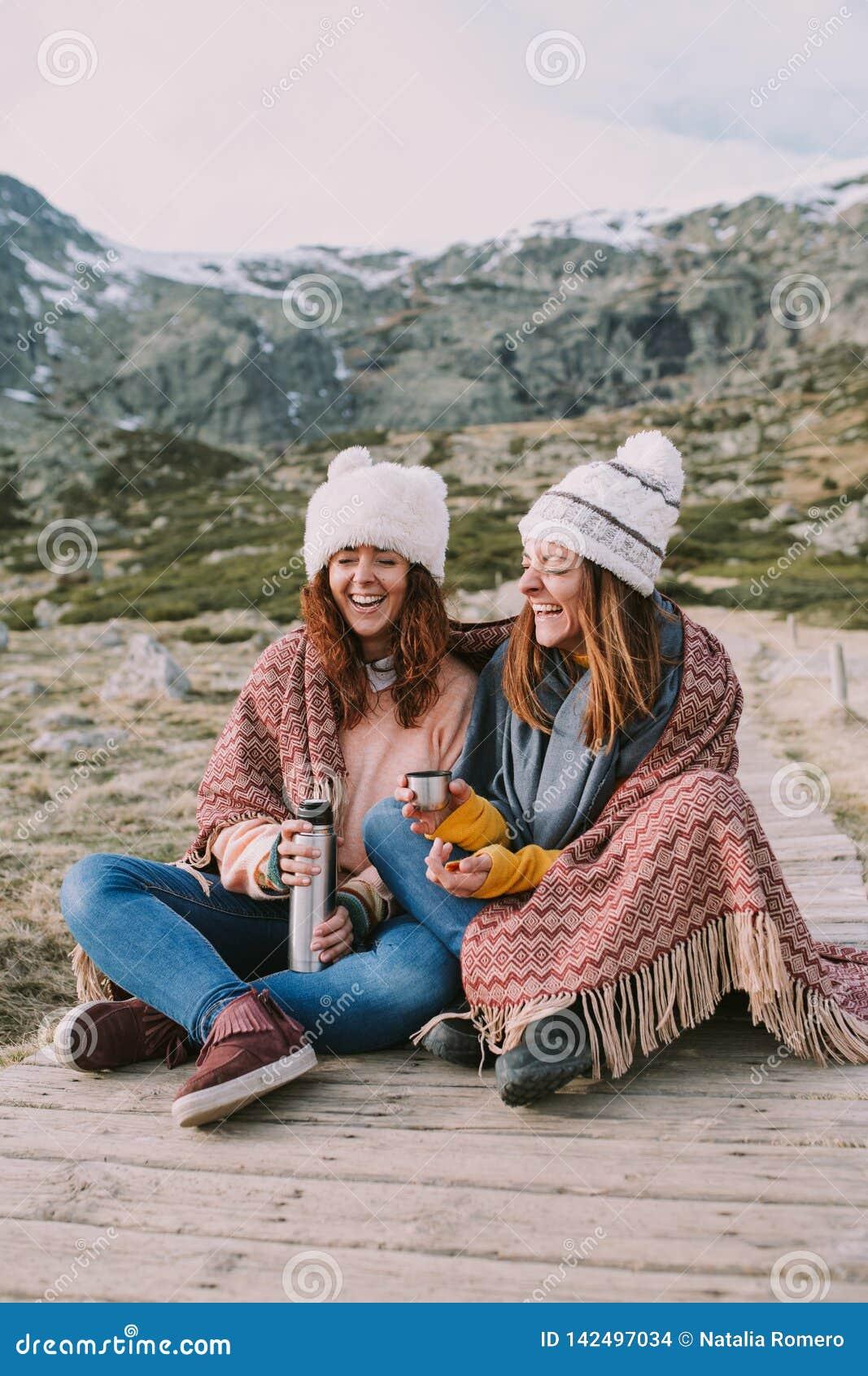 Dwa młodej kobiety słuzyć termos i gorącą filiżankę