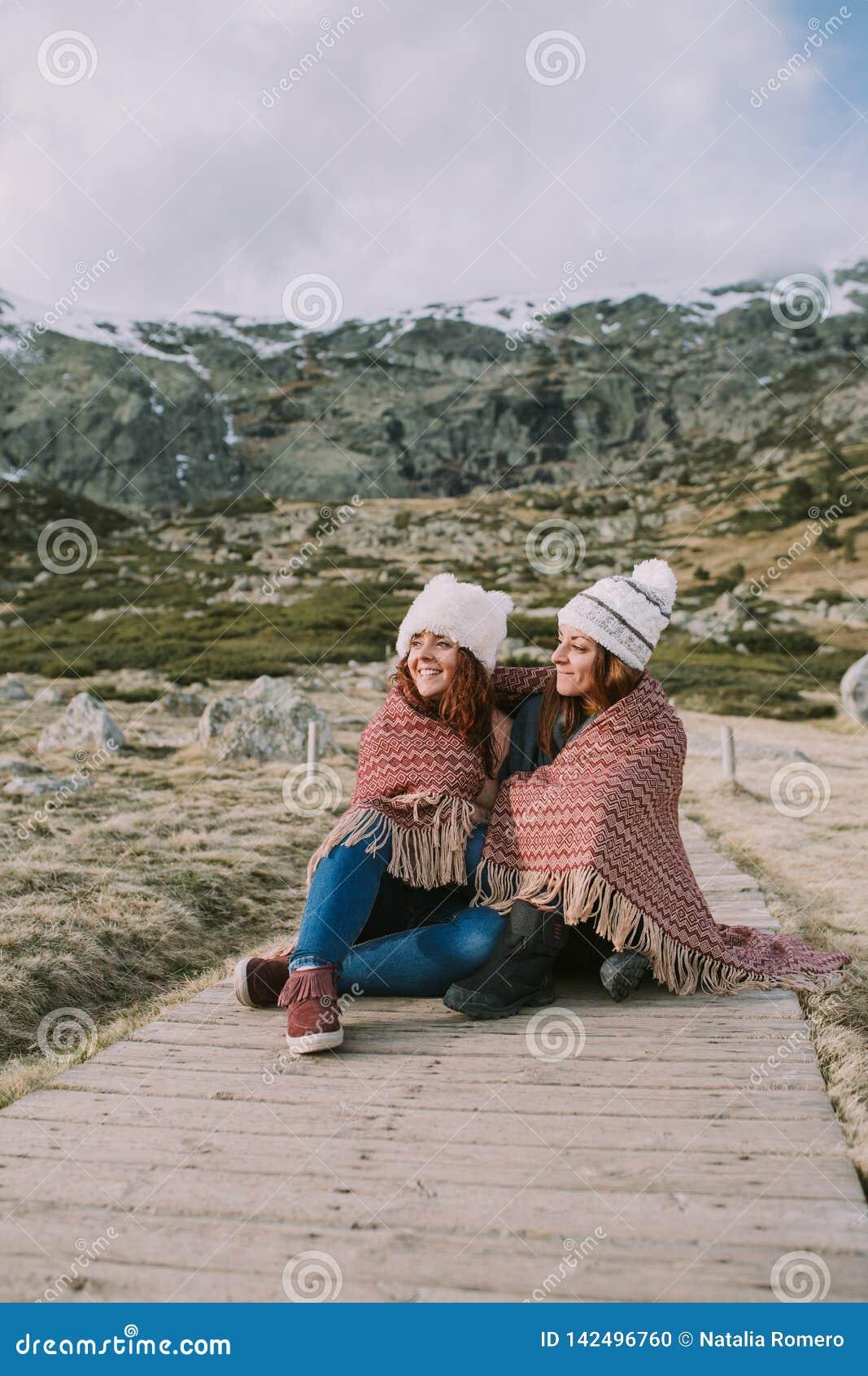 Dwa młodej kobiety siedzą na górze z koc