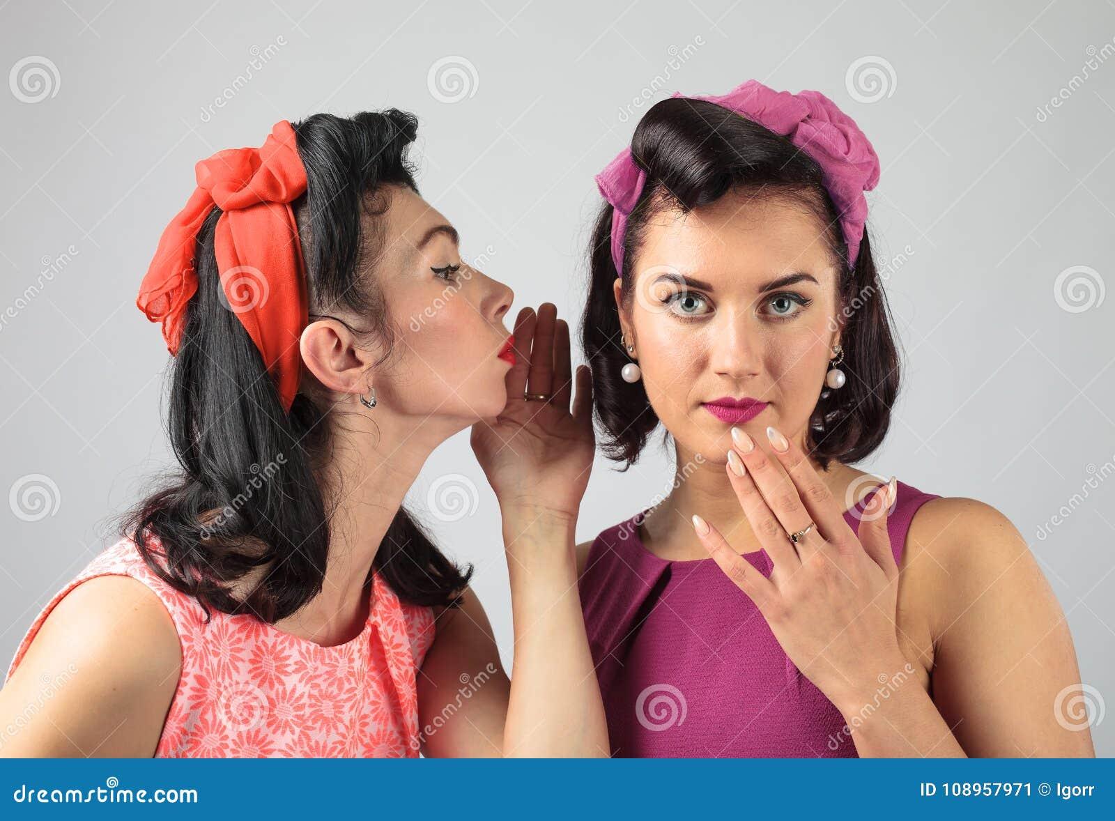 Dwa młodej kobiety szepcze plotki