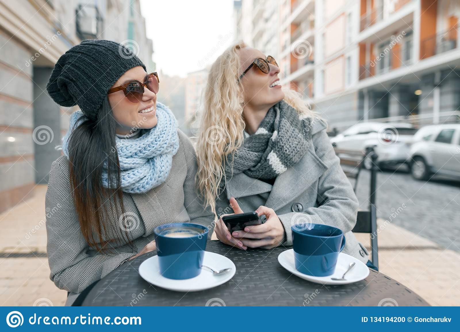 Dwa młodej one uśmiechają się modnej kobiety śmia się w plenerowej kawiarni, pijący kawę, opowiadający, tło miejskie