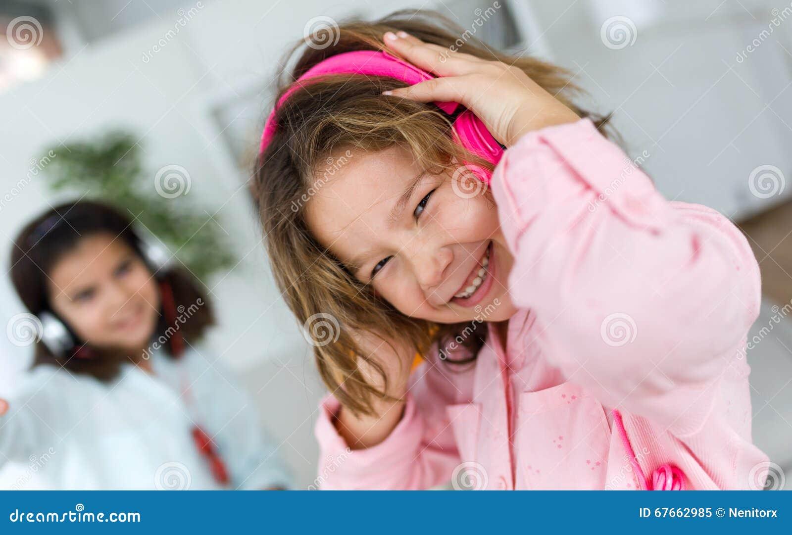 Dwa młodej siostry słucha muzyka i taniec w domu