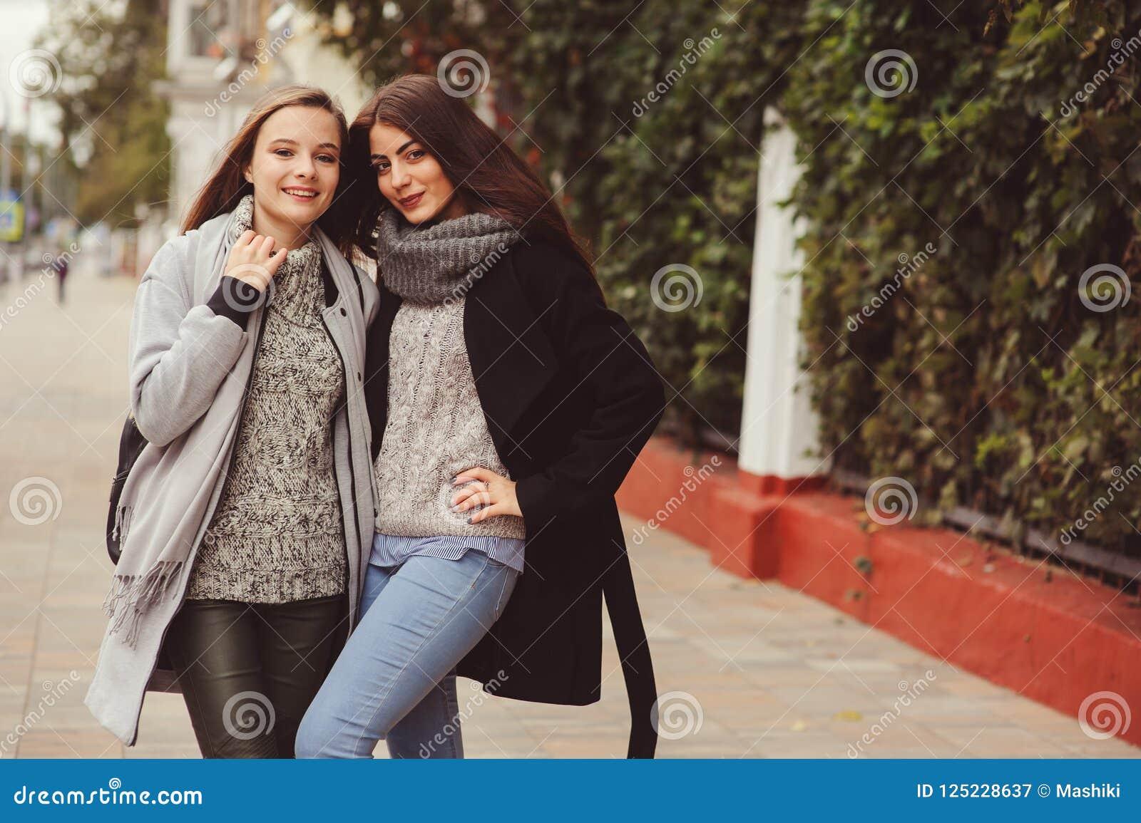 Dwa młodej szczęśliwej dziewczyny chodzi na miasto ulicach w przypadkowych moda strojach