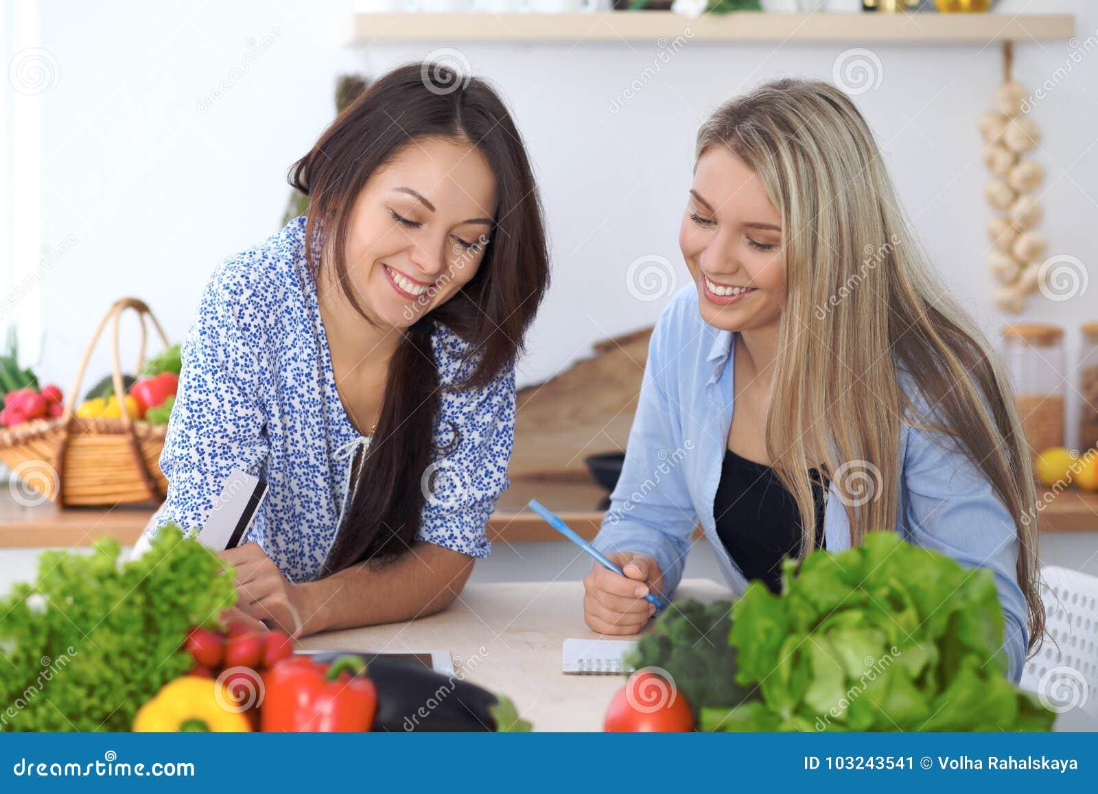 Dwa młodej szczęśliwej kobiety robi online zakupy dla robić menu pastylka komputerem Przyjaciele gotuje w kuchni