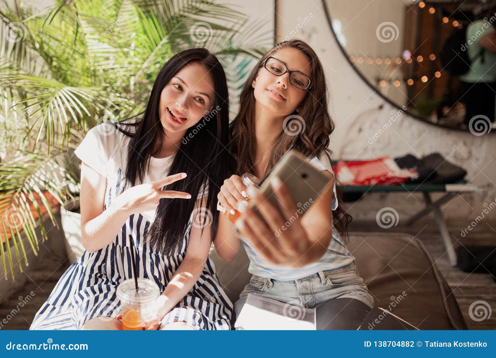 Dwa młodocianej uśmiechniętej pięknej szczupłej dziewczyny z długim ciemnym włosy, jest ubranym przypadkowych ubrania, siedzą obo