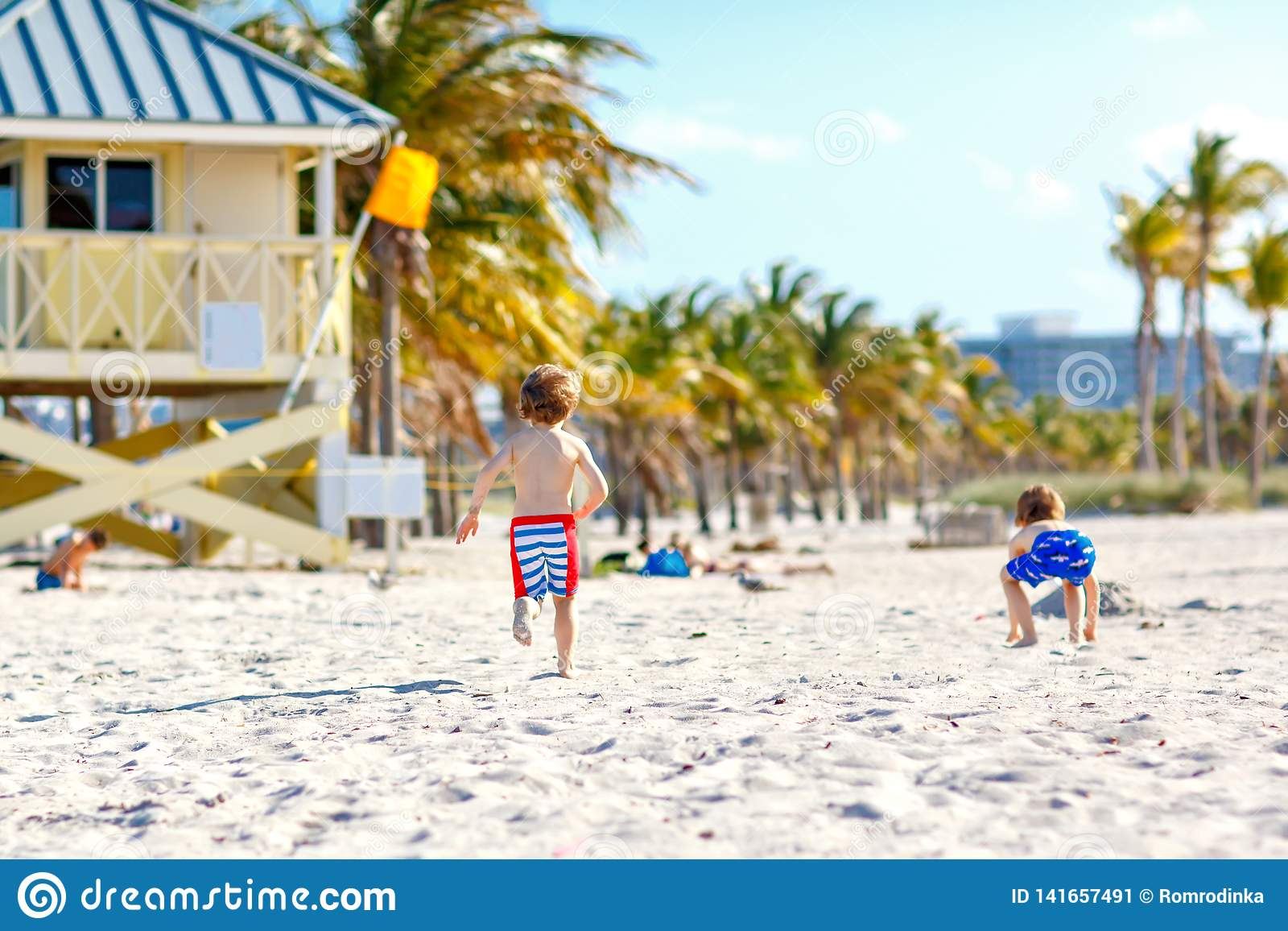 Dwa małe dziecko chłopiec ma zabawę na tropikalnej plaży, szczęśliwi najlepsi przyjaciele bawić się z piaskiem, przyjaźni pojęcie