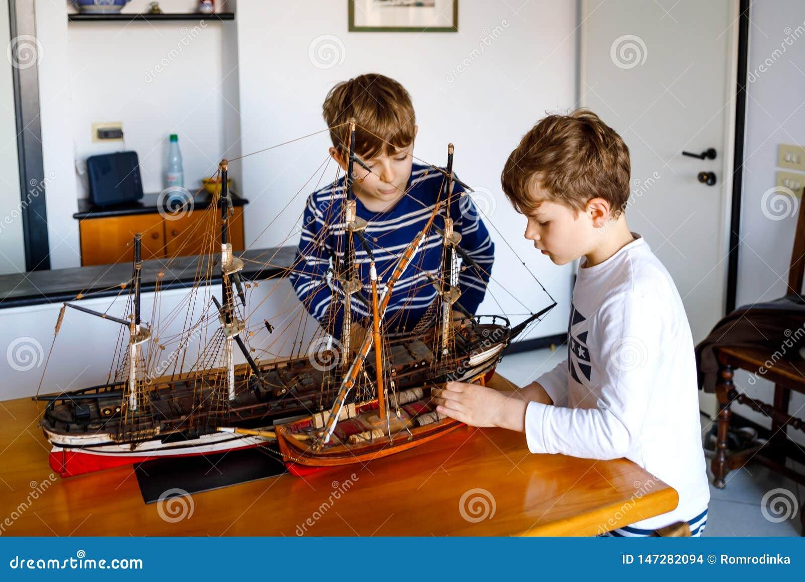 Dwa małe dziecko chłopiec bawić się z żeglowanie statku modelem indoors Z podnieceniem dzieci, rodzeństwa i najlepszy przyjaciele
