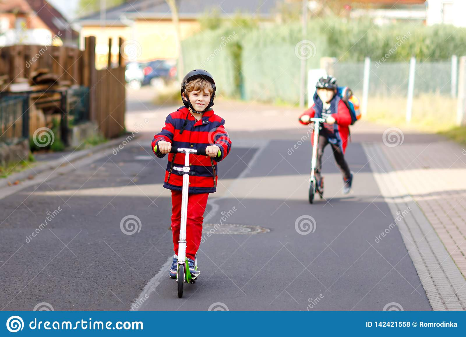 Dwa małe dziecko chłopiec jedzie na pchnięcie hulajnoga na sposobie do lub z szkoły Ucznie jedzie przez deszczu 7 rok
