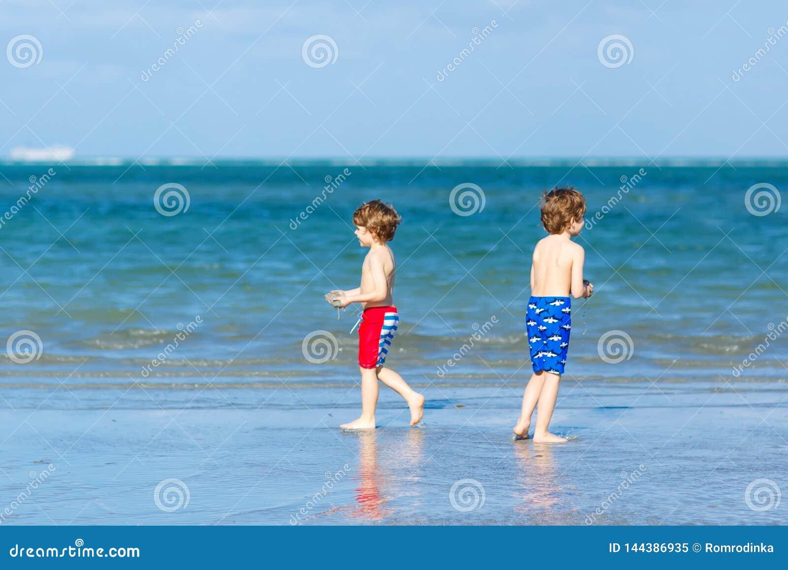 Dwa małe dziecko chłopiec ma zabawę na tropikalnej plaży, szczęśliwi najlepsi przyjaciele bawić się, przyjaźni pojęcie Rodzeństwo