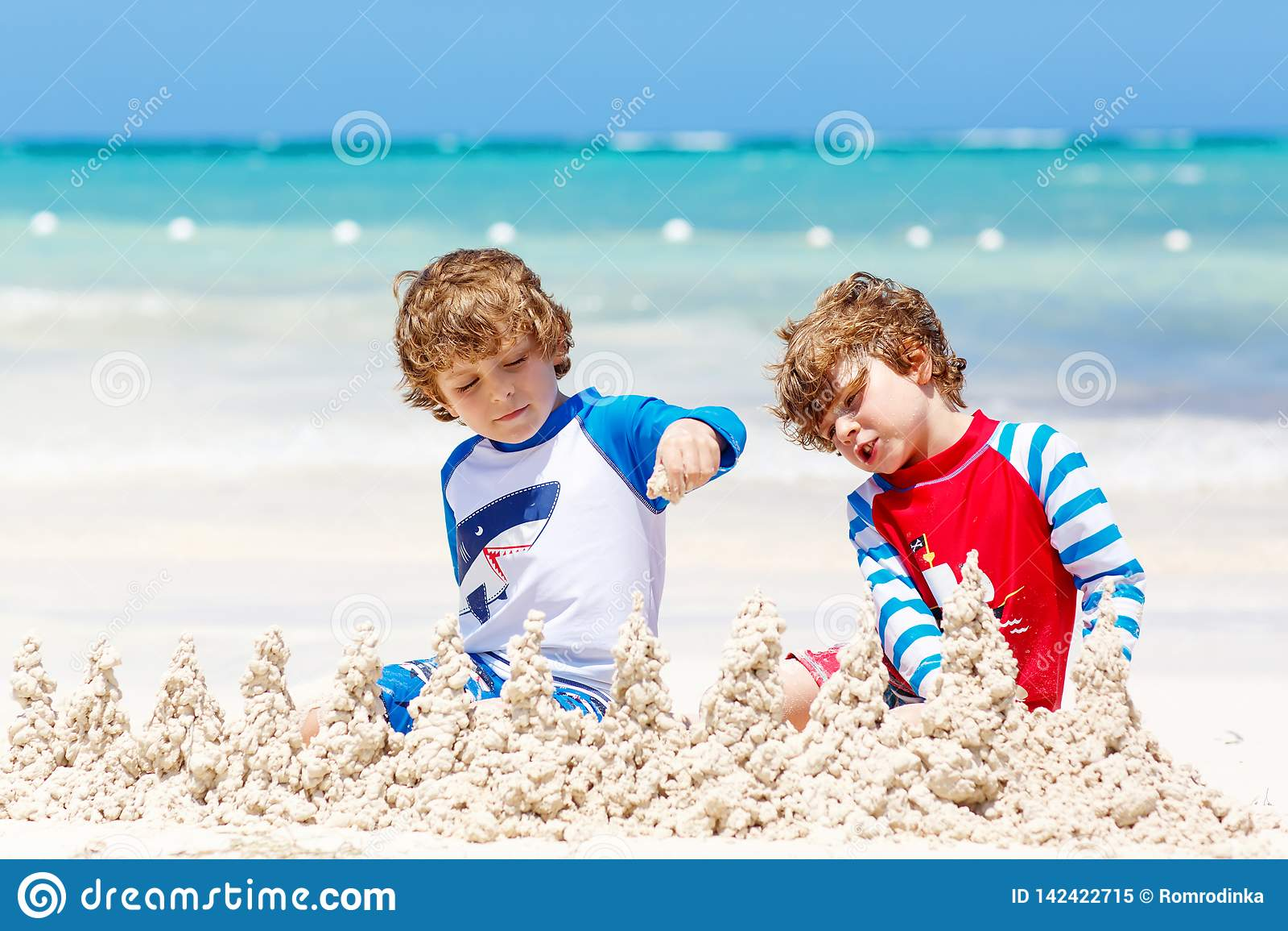 Dwa małe dziecko chłopiec ma zabawę z budować piaska kasztel na tropikalnej plaży carribean wyspa dzieci bawić się