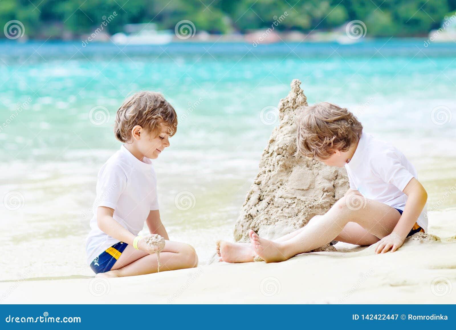 Dwa małe dziecko chłopiec ma zabawę z budować piaska kasztel na tropikalnej plaży Seychelles dzieci bawić się wpólnie