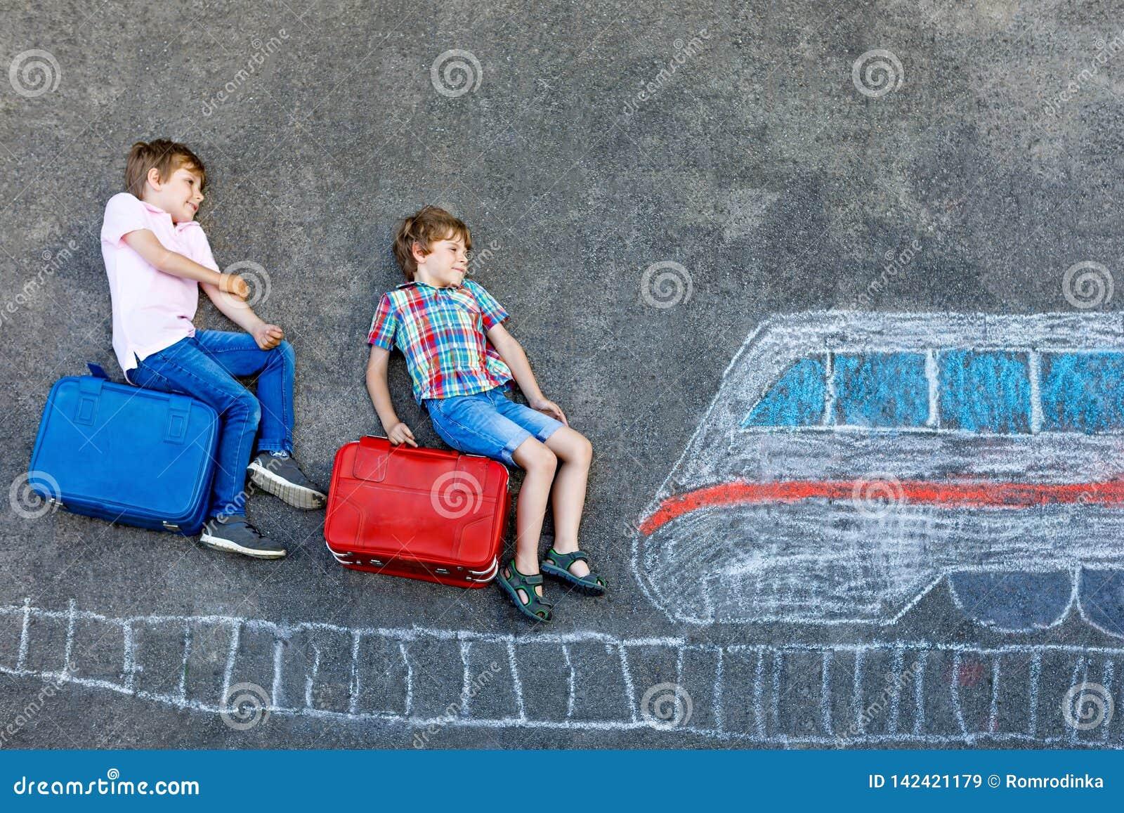 Dwa małe dziecko chłopiec ma zabawę z taborowym obrazka rysunkiem z kolorowym piszą kredą na asfalcie Dzieci ma zabawę z