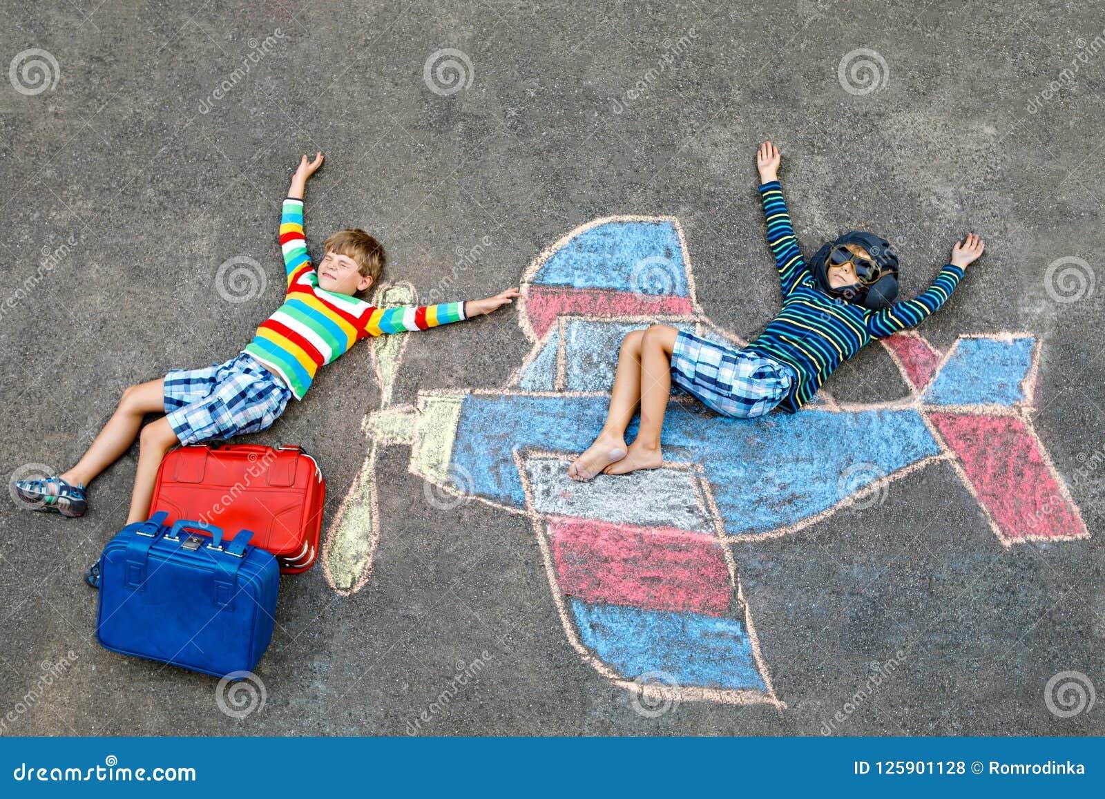 Dwa małego dziecka, dzieciak chłopiec ma zabawę z z samolotowym obrazka rysunkiem z kolorowym piszą kredą na asfalcie przyjaciele