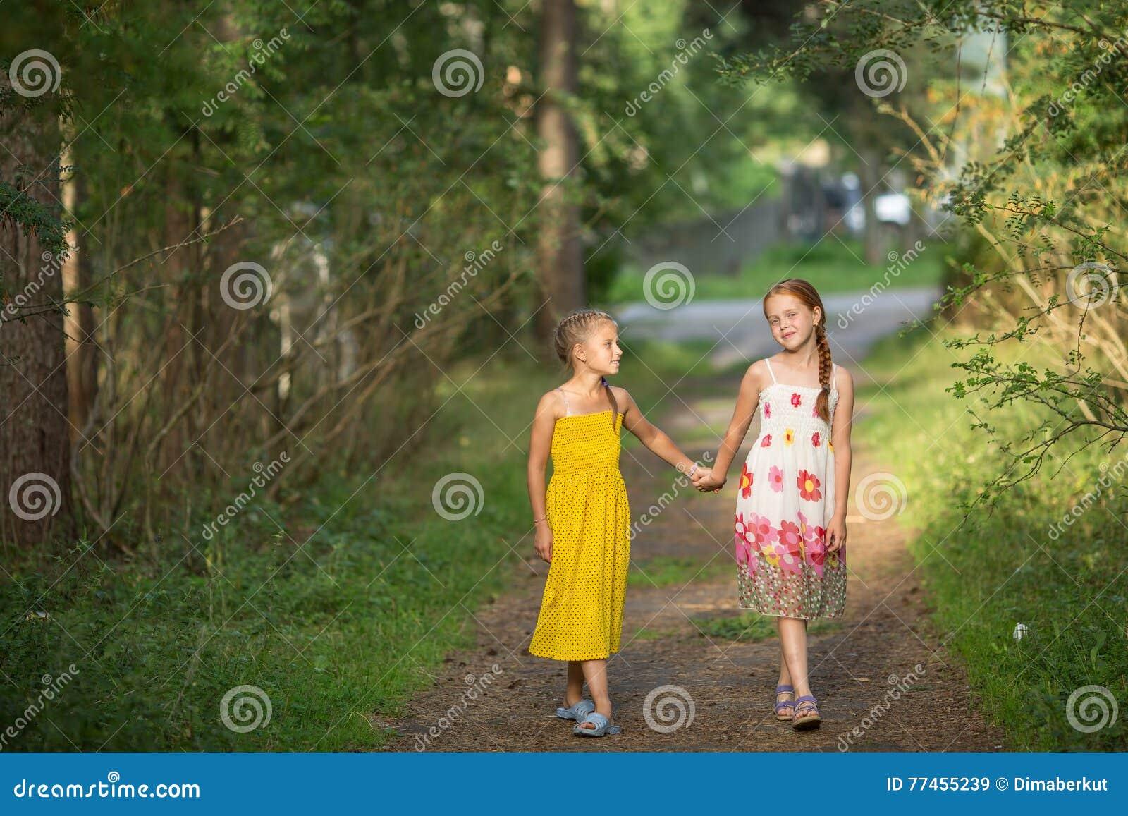 Dwa małej dziewczynki iść dla rękojeści na zielonej alei Chodzić