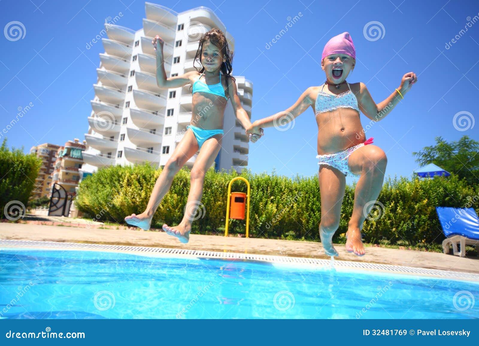 Dwa małej dziewczynki trzyma ręki zabawy doskakiwanie w pływackiego basen