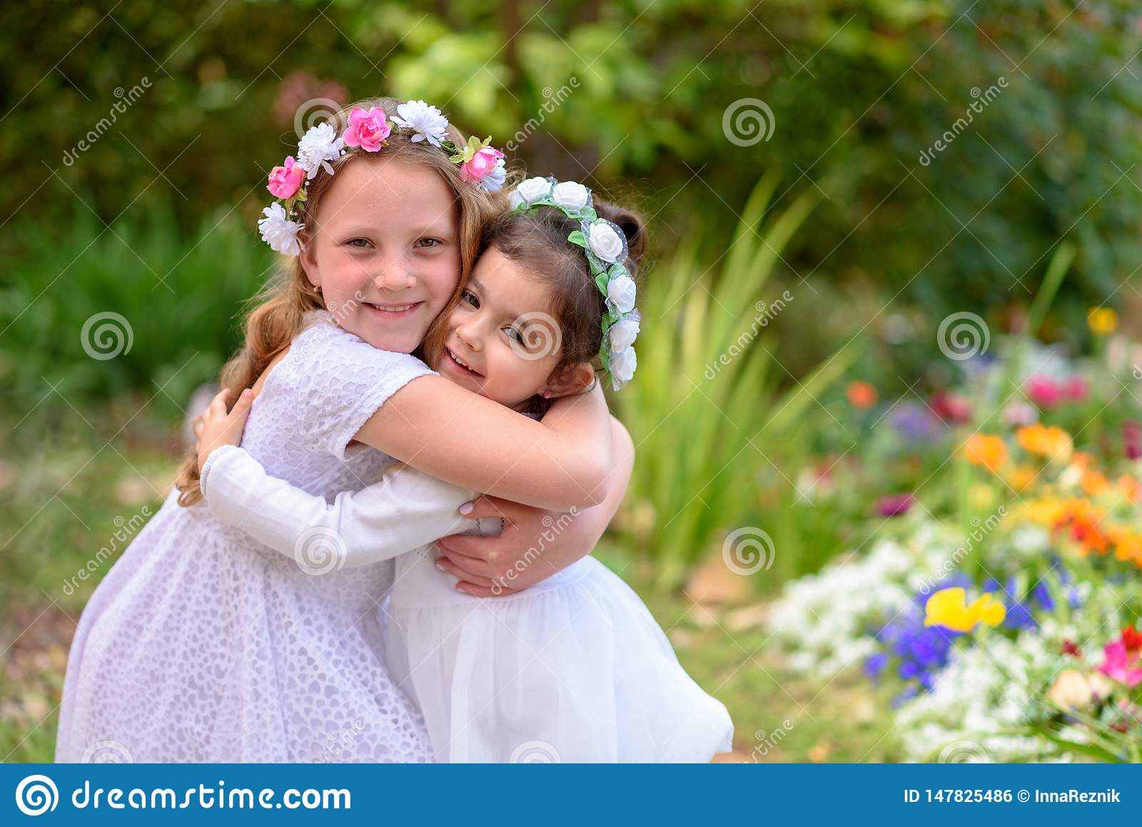 Dwa małej dziewczynki w białych sukniach ma zabawę lato ogród