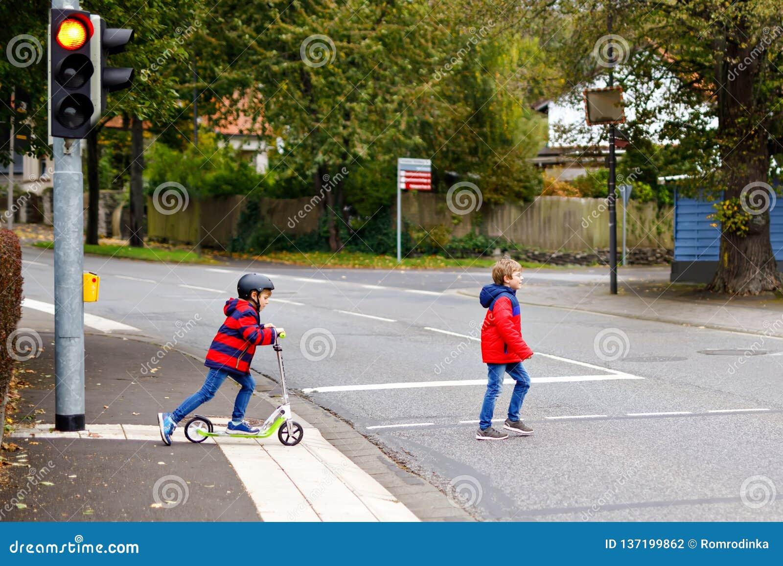 Dwa małej schoolkids chłopiec biega i jedzie na hulajnoga na jesień dniu Szczęśliwi dzieci w kolorowych ubraniach i miasto