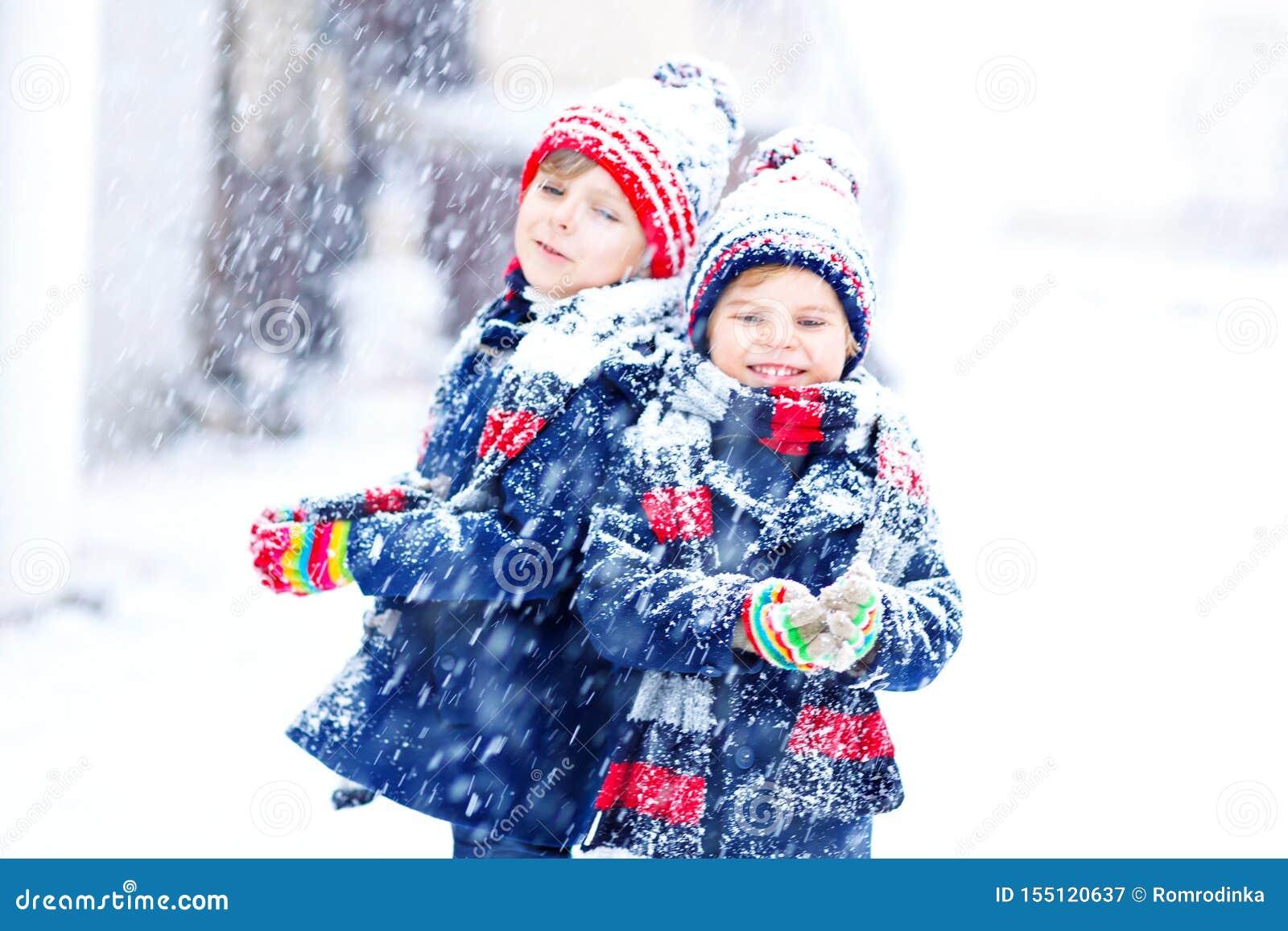 Dwa ma?e dziecko ch?opiec w kolorowej modzie odziewaj? bawi? si? outdoors podczas silnego opadu ?niegu Aktywny czas wolny z dzie?