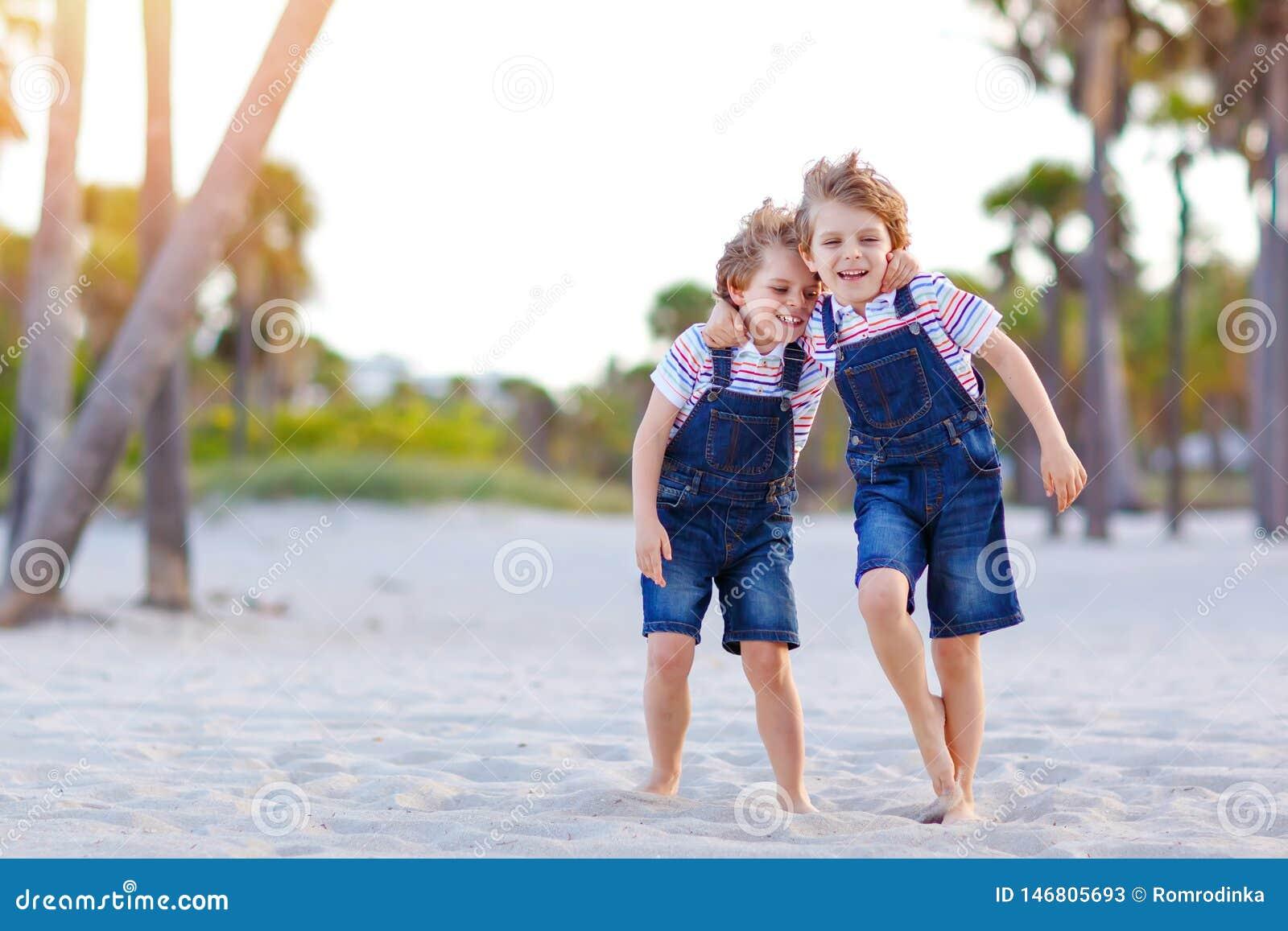 Dwa ma?e dziecko ch?opiec ma zabaw? na tropikalnej pla?y, szcz??liwi najlepsi przyjaciele bawi? si?, przyja?ni poj?cie Rodze?stwo