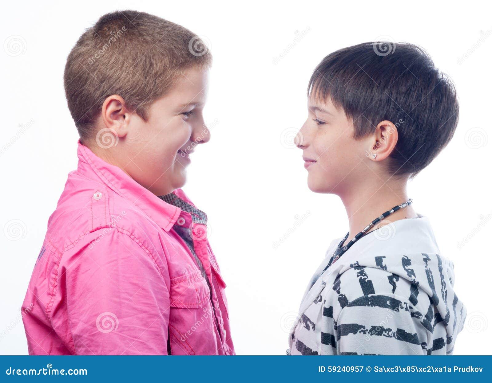 Dwa nastoletniego chłopaka ono uśmiecha się przy each inny odizolowywającym na bielu