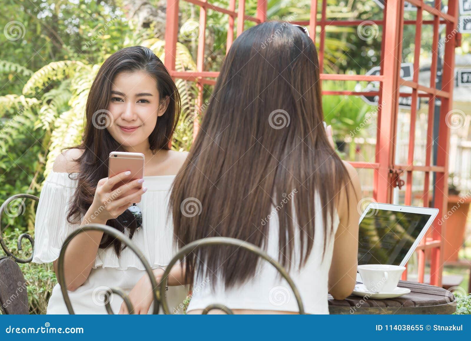 Dwa nastoletniej kobiety spotykają w sklep z kawą use smartphone i laptopie