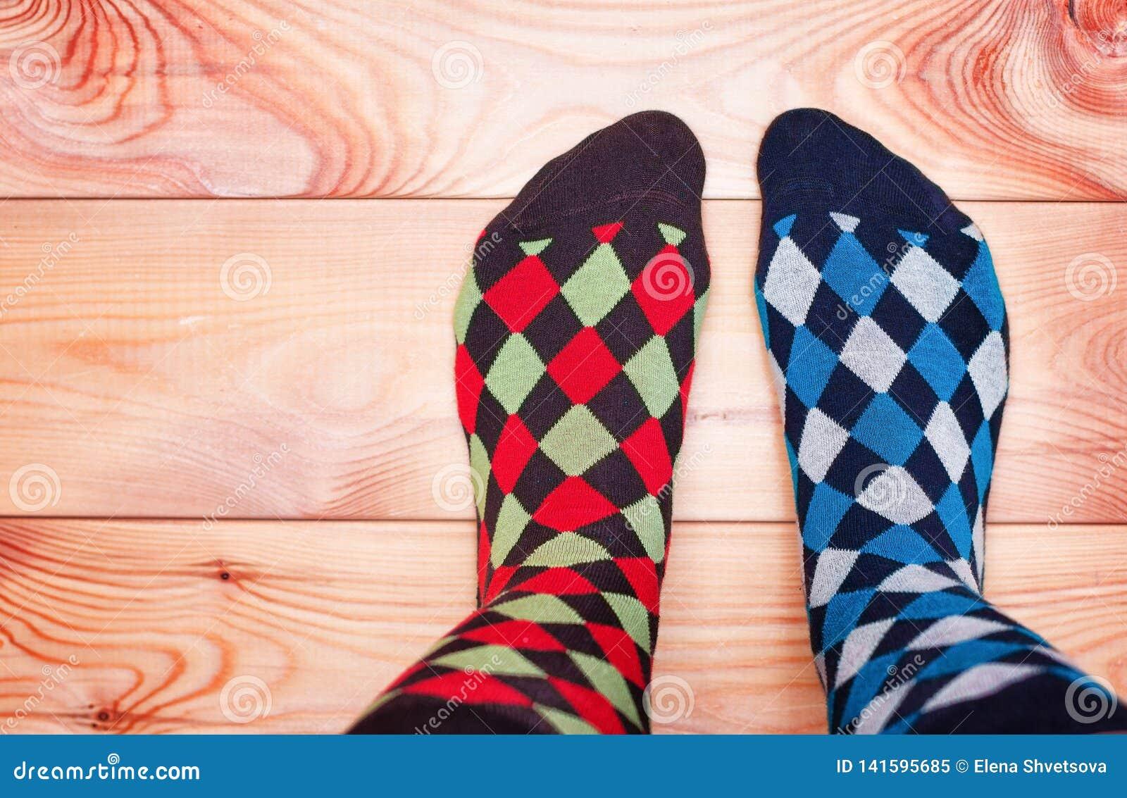 Dwa nogi w różnych pstrobarwnych skarpetach na drewnianej podłodze