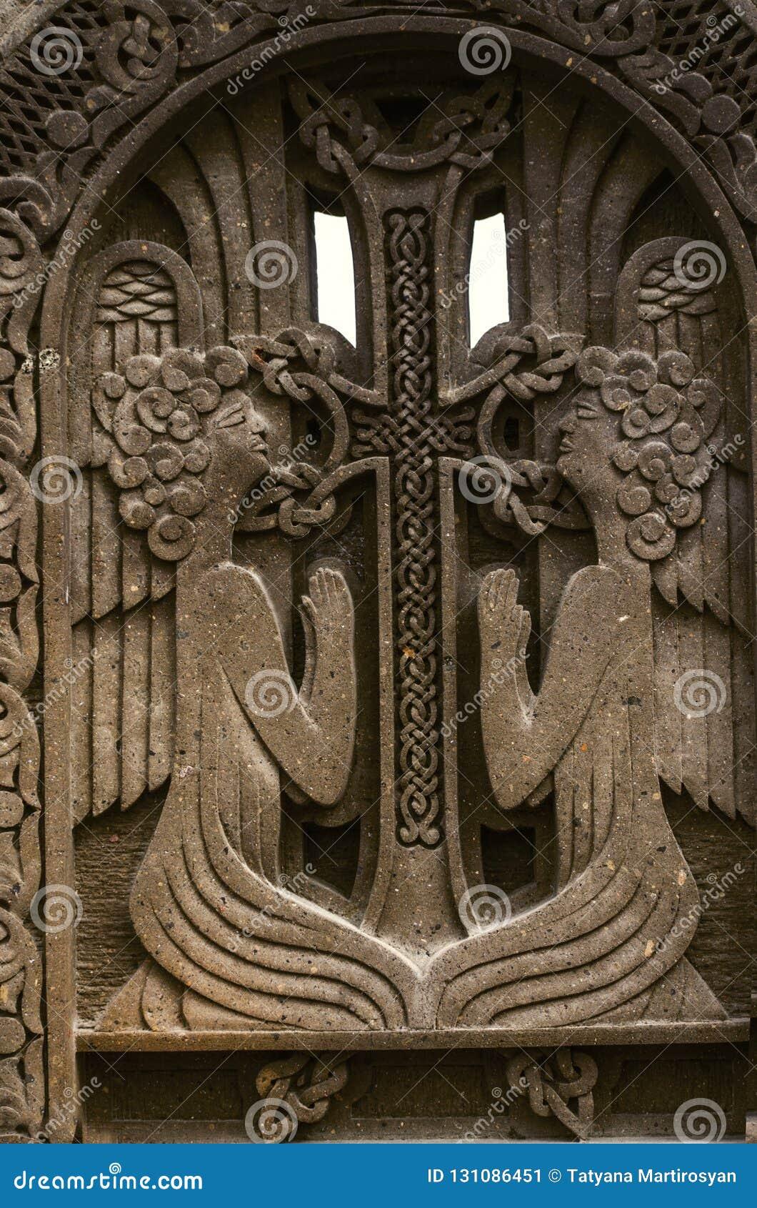 Dwa one modlą się anioła blisko krzyża z przeplatać ornament, grawerującego na ciemnym powulkanicznym kamieniu