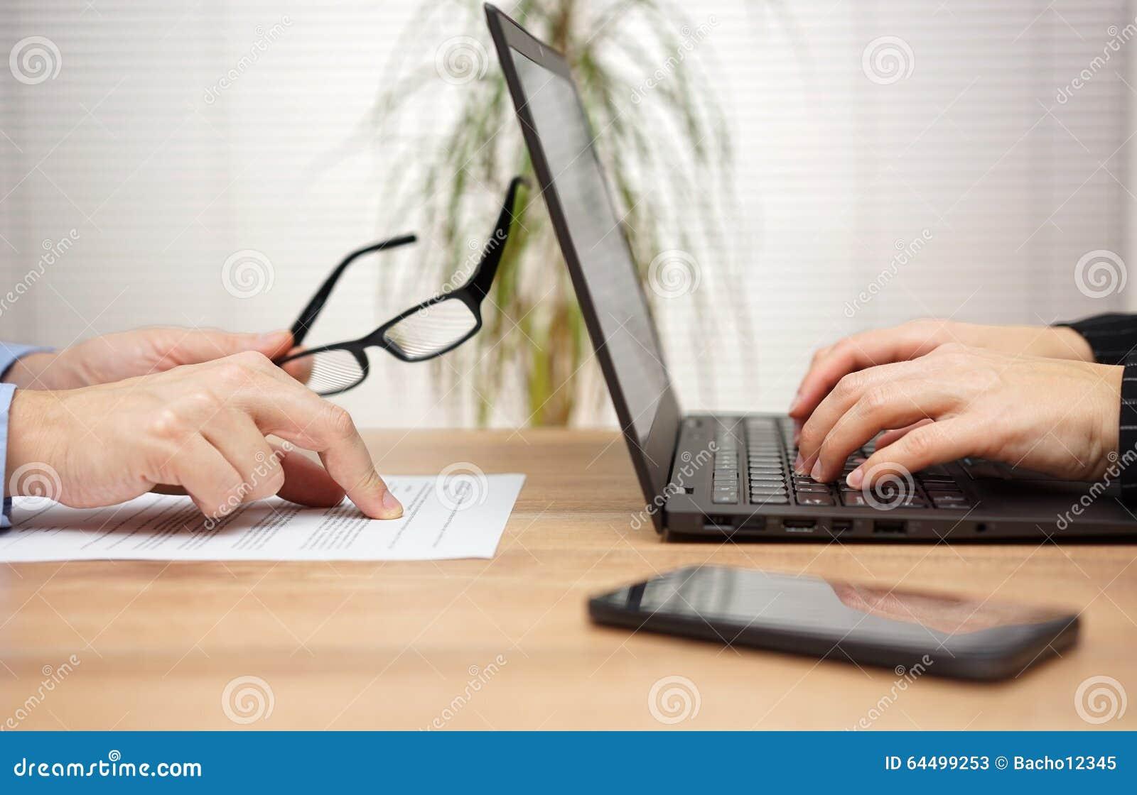Dwa partnera są egzamininujący dokument w biurze i przeglądający, wom