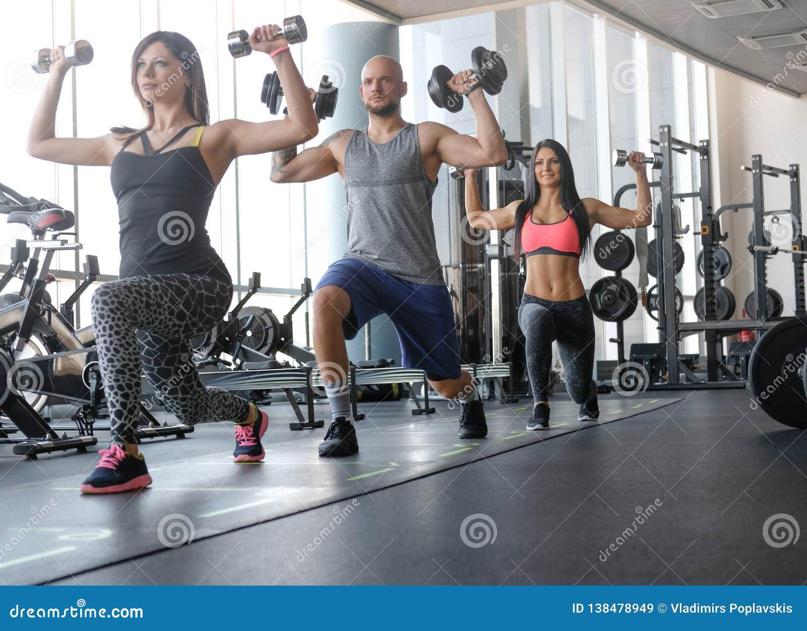 Dwa pięknej dziewczyny z ich trenerem robi czynnościowemu crossfit szkoleniu z dumbbells w gym