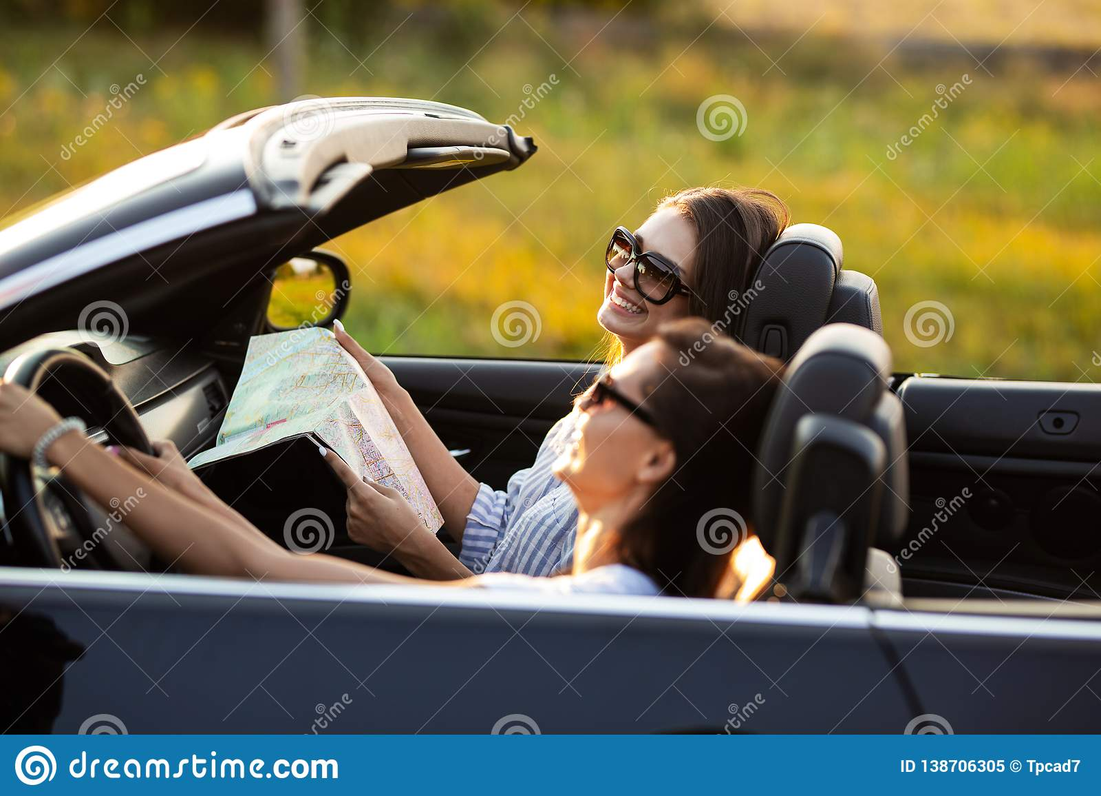 Dwa pięknej młodej kobiety w okularach przeciwsłonecznych są siedzący w czarnym kabriolecie i ono uśmiecha się na słonecznym dniu