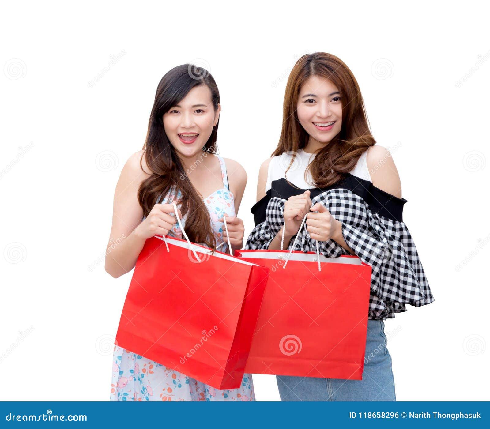 Dwa pięknej uśmiechniętej azjatykciej młodej kobiety z zakupy sprzedaży torbami odizolowywać