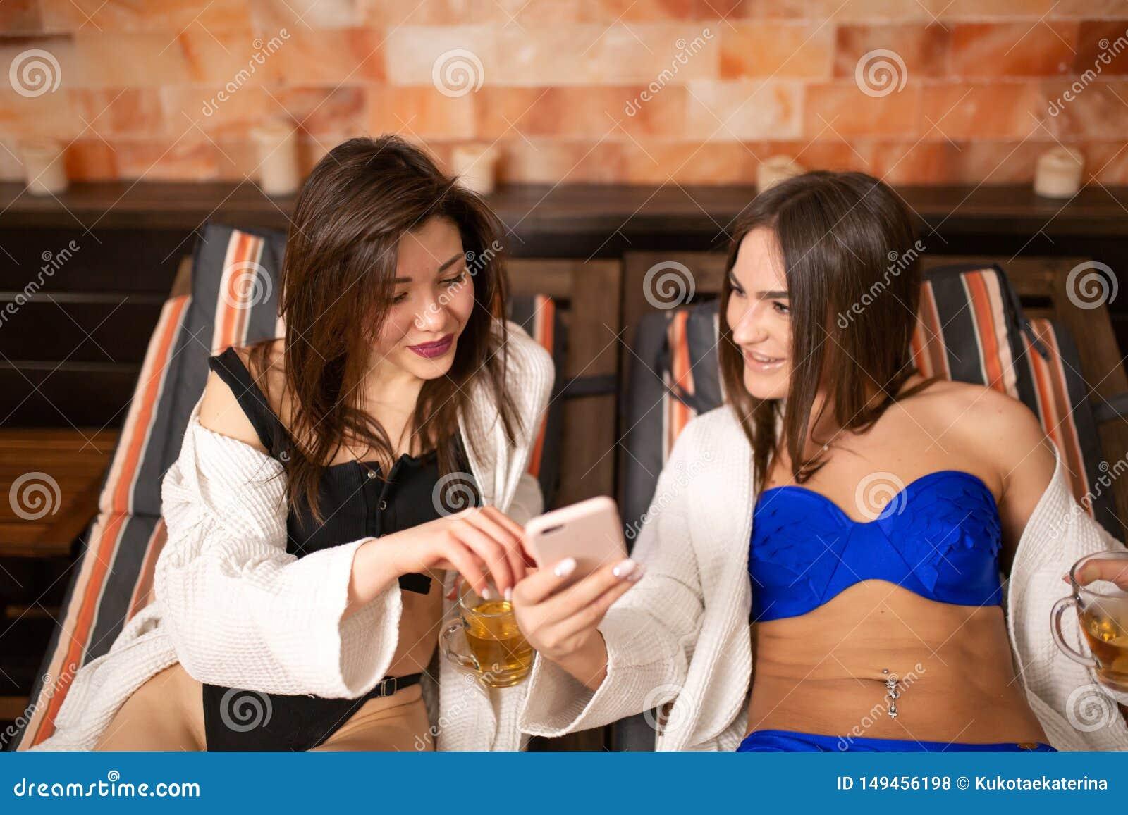 Dwa pi?knej m?odej dziewczyny w swimsuits k?a?? na drewnianym lounger w sauna dyskutuj? wiadomo?? podczas gdy patrzej?cy w telefo
