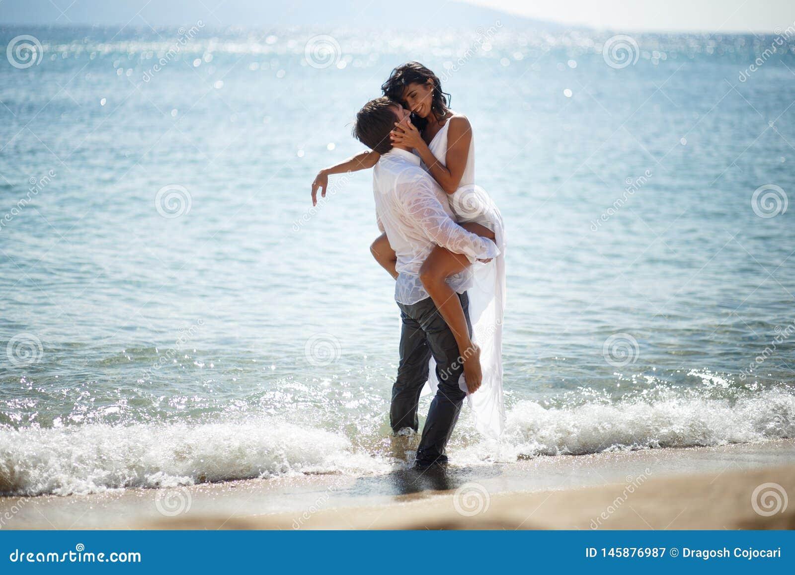 Dwa poślubiali młodych dorosłych, mężczyźni trzyma jego żony żarliwie, siedzący w wodzie, odizolowywającej na seascape tle
