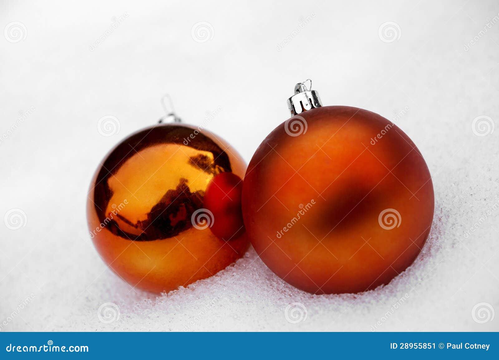 Dwa Pomarańczowego Baubles w śniegu