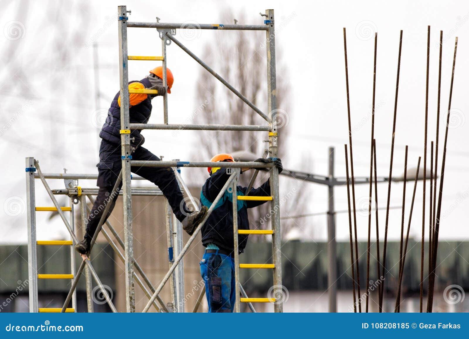 Dwa pracowników budowy metalu rusztowanie na budowie